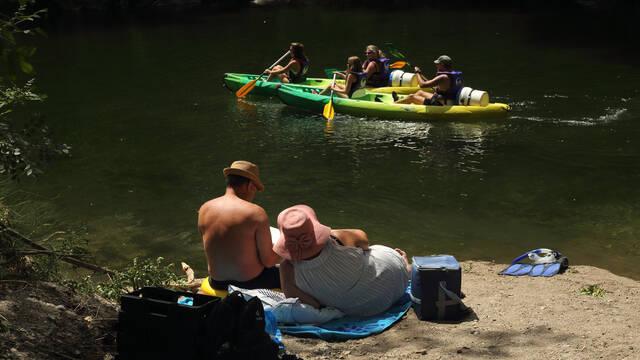 un couple se repose le long de l'Orb, un groupe passe en canoë