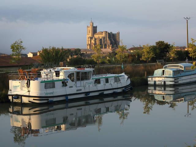 Péniche sur le canal du Midi et la collégiale de Capestang en arrière plan ©G.Souche